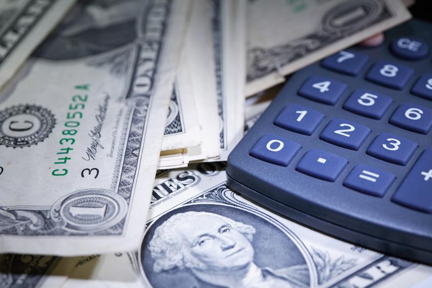 Financial background. Closeup of one dollar notes near calculator